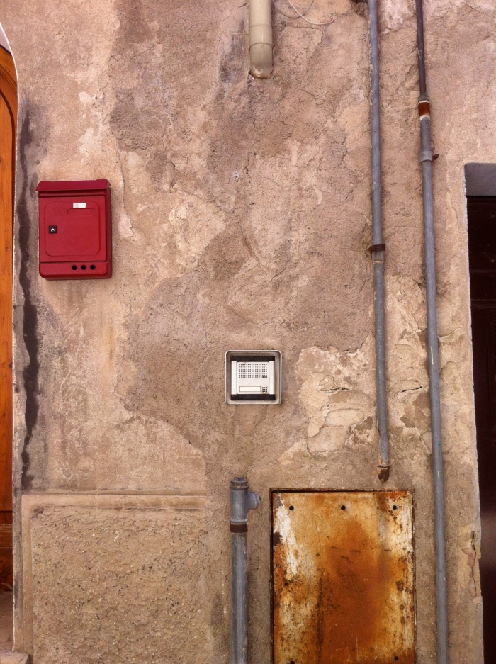 Red letterbox, panel and pipes
